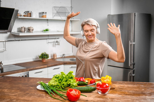 Mature woman dancing while cooking in kitchen