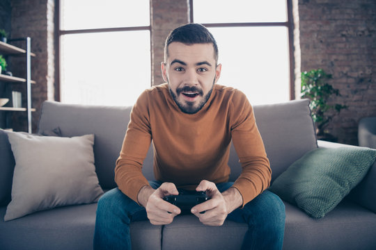 Portrait of his he nice-looking attractive bearded cheerful cheery addicted guy spending weekend sitting on divan playing xbox at industrial loft brick interior style living-room indoors