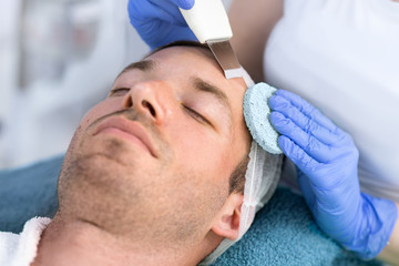Handsome man on treatment of facial skin