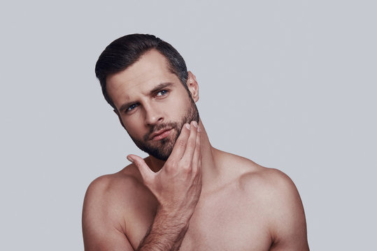 Time to shave. Handsome young man touching his beard while standing against grey background