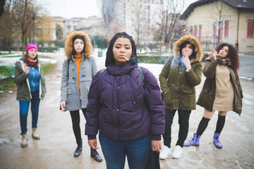 group of young multiracial women smoking cigarette in the street