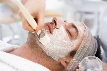 Attractive man with facial cream lying and relaxing at spa