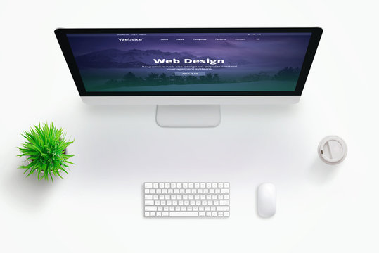 Web design studio desk with monitor and web site presentation. Copy space in the middle for text. Flat lay.