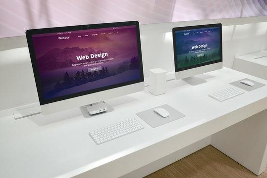 Web design development studio with two monitors and web site presentations.