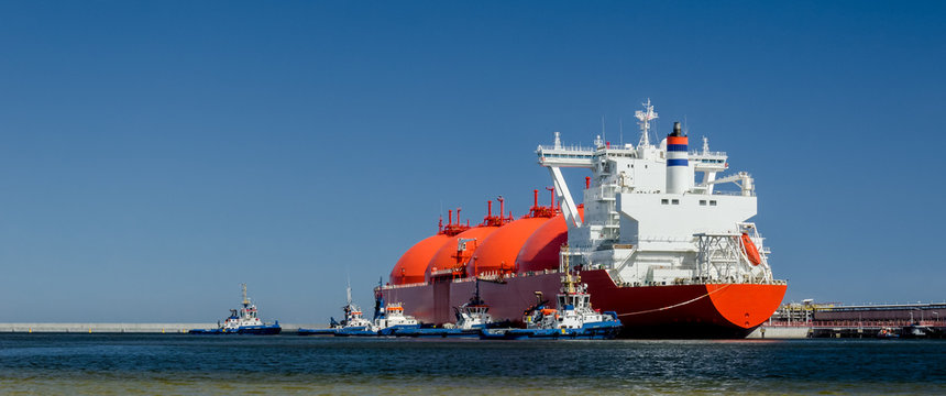 RED LNG TANKER AND SWARM OF TUGBOATS - A giant ship moored to the gas terminal in Swinoujscie
