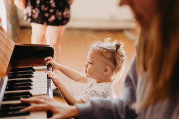 Mother teaches a little girl to play the piano. They play and sing songs. Its fun, Cute happy child girl playing piano in a light room. Selective focus, noise effect