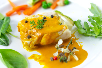 Plate of Steamed fish with curry sauce with salad