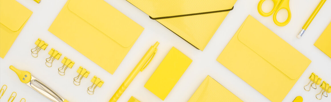 panoramic shot of yellow pen, pencils, paper clips, eraser, stickers, envelopes, stickers, folder, scissors and compasses isolated on white