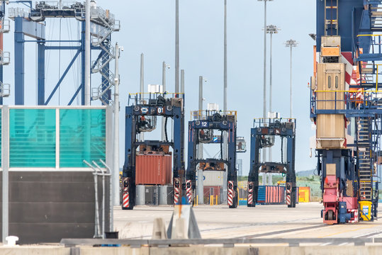 straddle carrier picking up containers at port botany