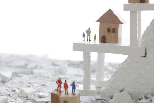 災害で急な崖の斜面に取り残された家と人々