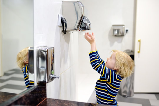 Little caucasian boy drying his hands in a restroom