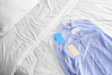 Clothes after dry-cleaning on bed