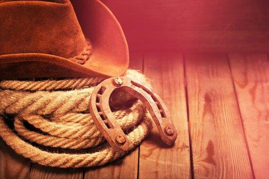 Old horseshoe , lariat lasso and cowboy hat on background