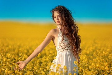 Beautiful carefree girl with long curly healthy hair over Yellow rape field landscape background. Attracive brunette with blowing hairstyle enjoying sunset, outdoor beauty portrait. Wall mural