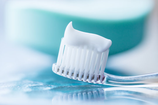 Plastic toothbrush with white toothpaste on a blue table
