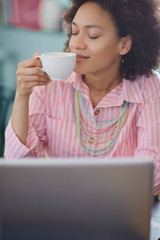 Charming mixed race woman in striped pink dress aitting in coffee shop, drinking coffee and using laptop.
