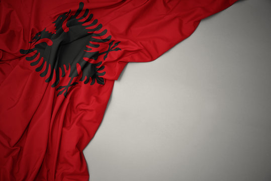 waving national flag of albania on a gray background.