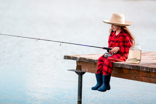 Cute little child girl in rubber boots and straw hat fishing from wooden pier near glass jar and little fish on a lake. Family leisure activity during summer day