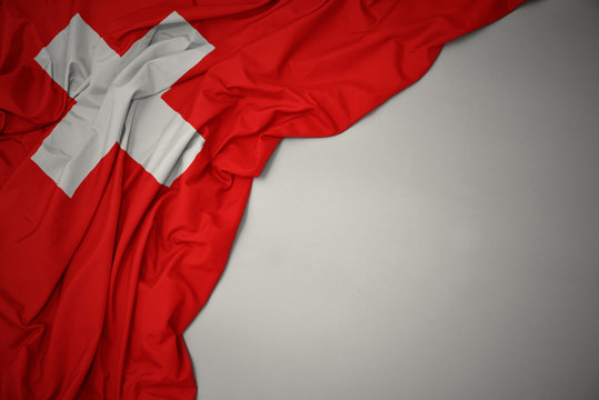 waving national flag of switzerland on a gray background.