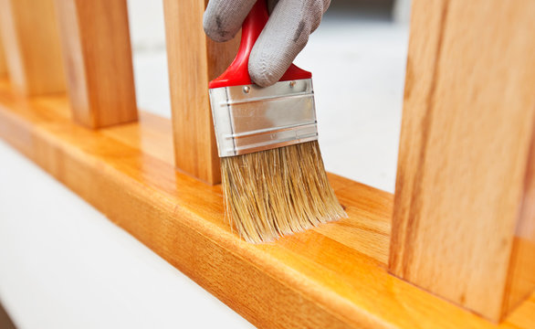 Woman paints a varnish wooden board by brush