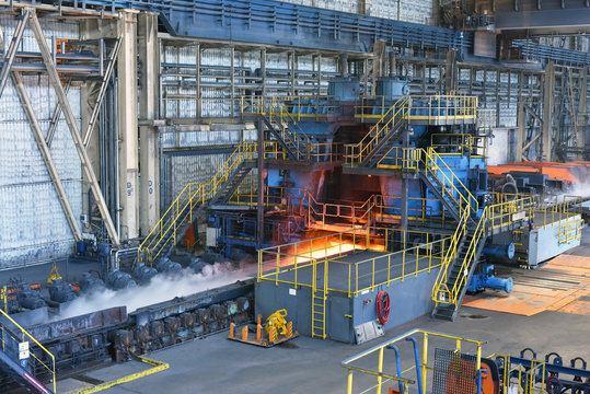machine with conveyor belt with glowing metal frame in the production line of a steel mill