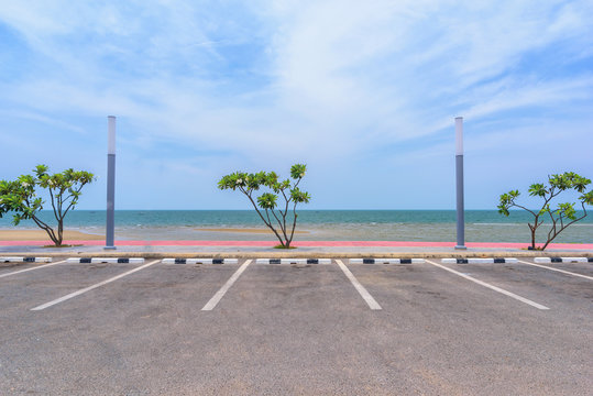 Empty parking lot against sea and beautiful blue sky.