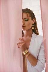 Obraz Attractive girl model with trend makeup and long hair in a white pantsuit and gold jewelry - fototapety do salonu