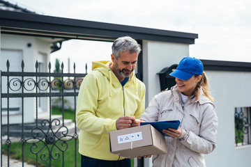 senior man receiving packages from courier