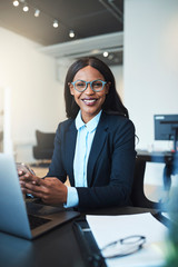 Smiling African American businesswoman sitting at work using a c
