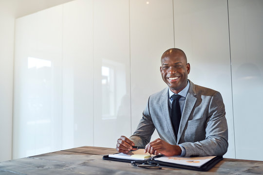 Smiling African American businessman sitting with paperwork in a