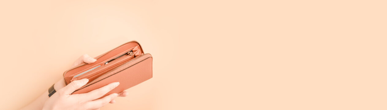 web banner design for woman fashion in spring and summer concept with beauty woman hand hold and open modern brown leather purse or wallet in left hand with pastel color background