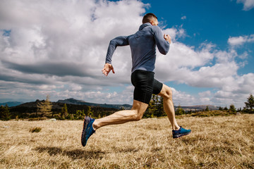 male runner fast running on mountain trail in summer outdoor