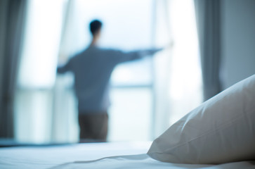 Bed made up with white pillows and bed sheets in cozy room. Young businessman standing at hotel window looking out. Focus on cushion. Rear view of man waking up to morning sun. Motivation concept.