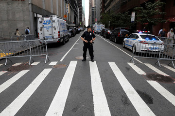 A New York City Police Department (NYPD) officer guards a closed street next to 787 7th Avenue one day after a helicopter crashed on the building's roof in New York