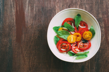 Spinach salad with colorful tomatoes balsamic sauce. Top view, wooden background, copy space