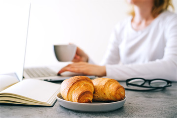 Croissants with coffee on the office table.  Business breakfast concept