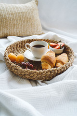 Breakfast in bed. Tray of coffee, croissants and berries on white blanket