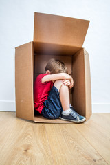 lonely child crying in box, feeling sad, rejected or scared
