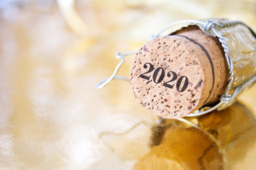 champagne cork with numbers 2020 on a blurry Christmas background, happy new year concept