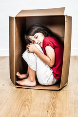 concept of small curled up sleeping child hunched in box
