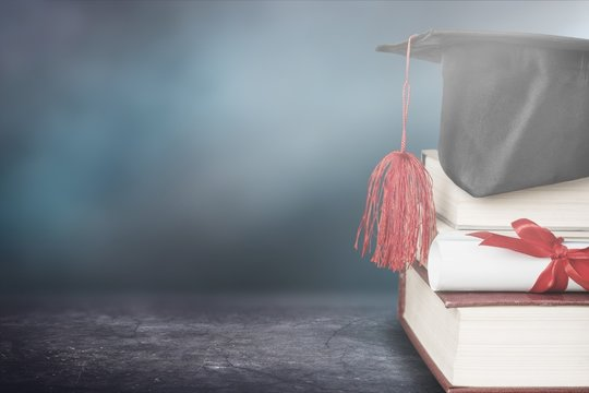 Graduation cap with stack books on desk