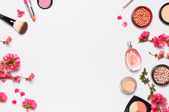 Different makeup cosmetic. Ball blush rouge face powder lipstick concealer bottle of perfume eyeshadow makeup brush spring pink flowers on light background top view flat lay. Beauty fashion background