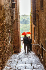 Spoed Foto op Canvas Smal steegje People walking with a red umbrella in a narrow alley