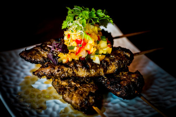 Char-grilled jerk marinated chicken tenders in skewers with fruit salsa on top