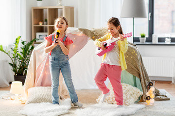 childhood, hygge and friendship concept - happy girls with guitar and microphone playing music and singing near kids tent or teepee at home Fotobehang