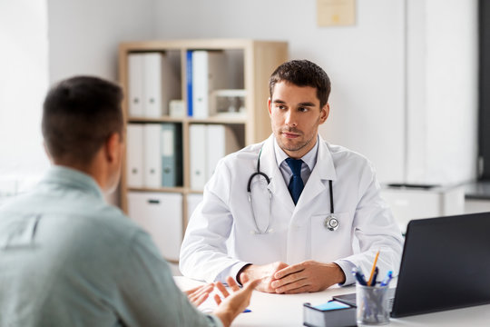 medicine, healthcare and people concept - doctor talking to male patient at medical office in hospital