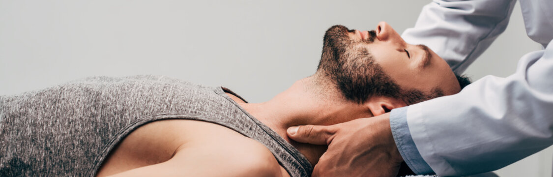 panoramic shot of chiropractor massaging neck of man on grey