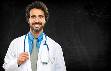Smiling doctor on a chalkboard background