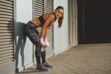 Young sports woman resting after workout outside in the city