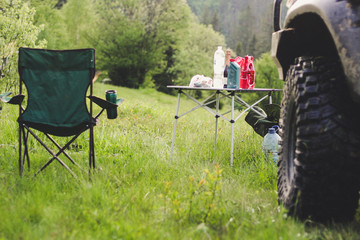 Picnic in the mountains with folding chairs and a table. The car and the rubber wheel. Carpathian mountains